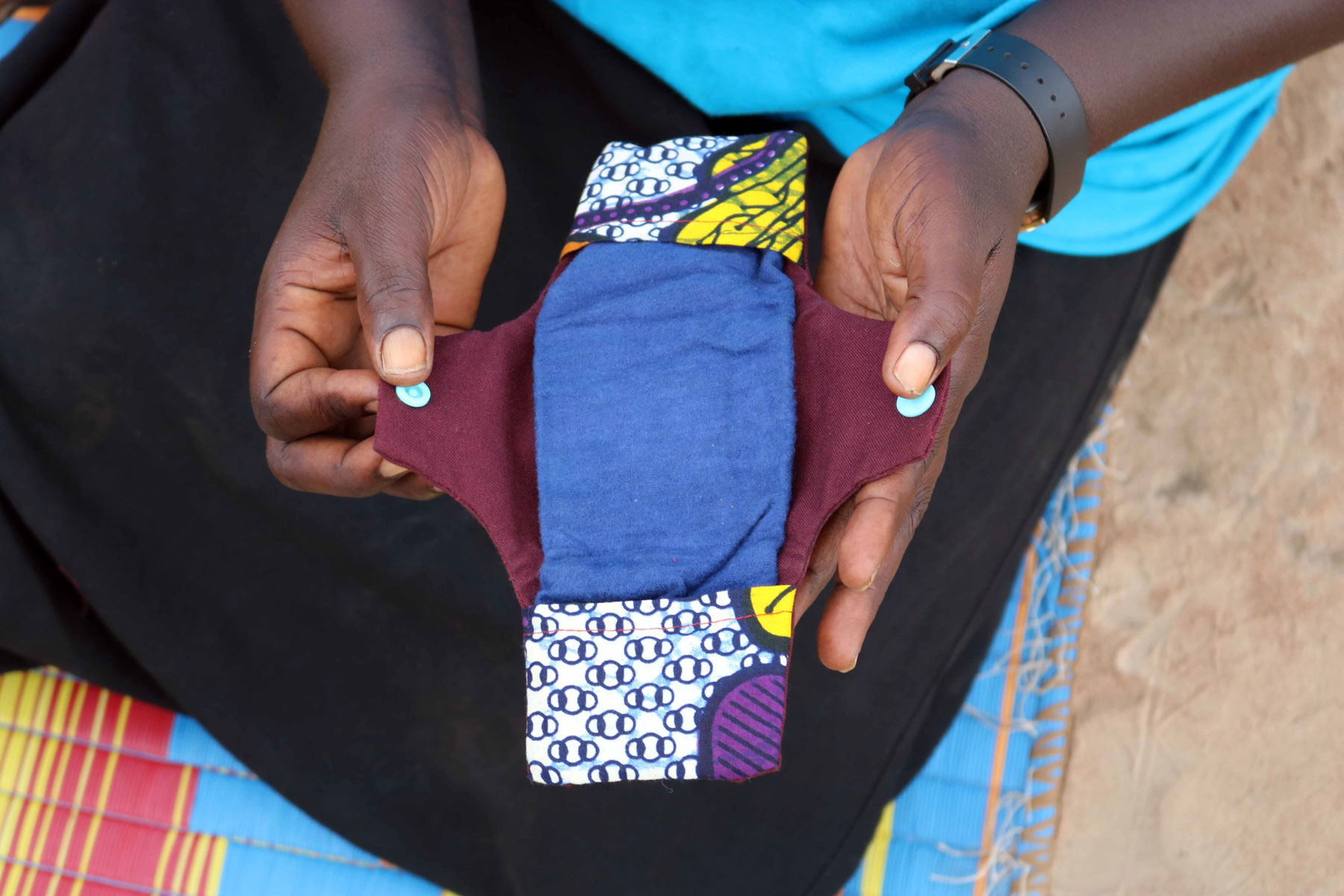 An LWF case worker shows a student how to sew reusable pads.