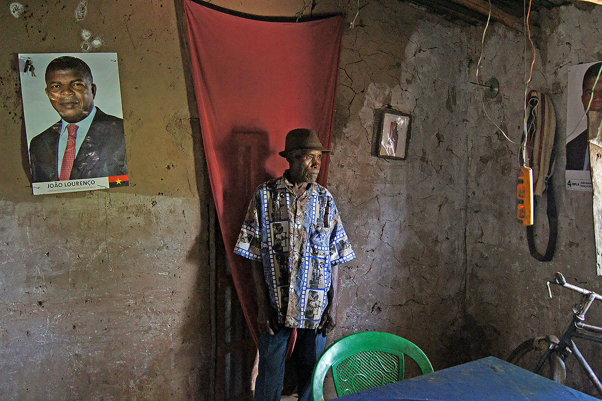 A farmer in his house in Moxico province, Angola. Like many others, he is a strong supporter of the ruling party and the president, who is depicted on the posters.
