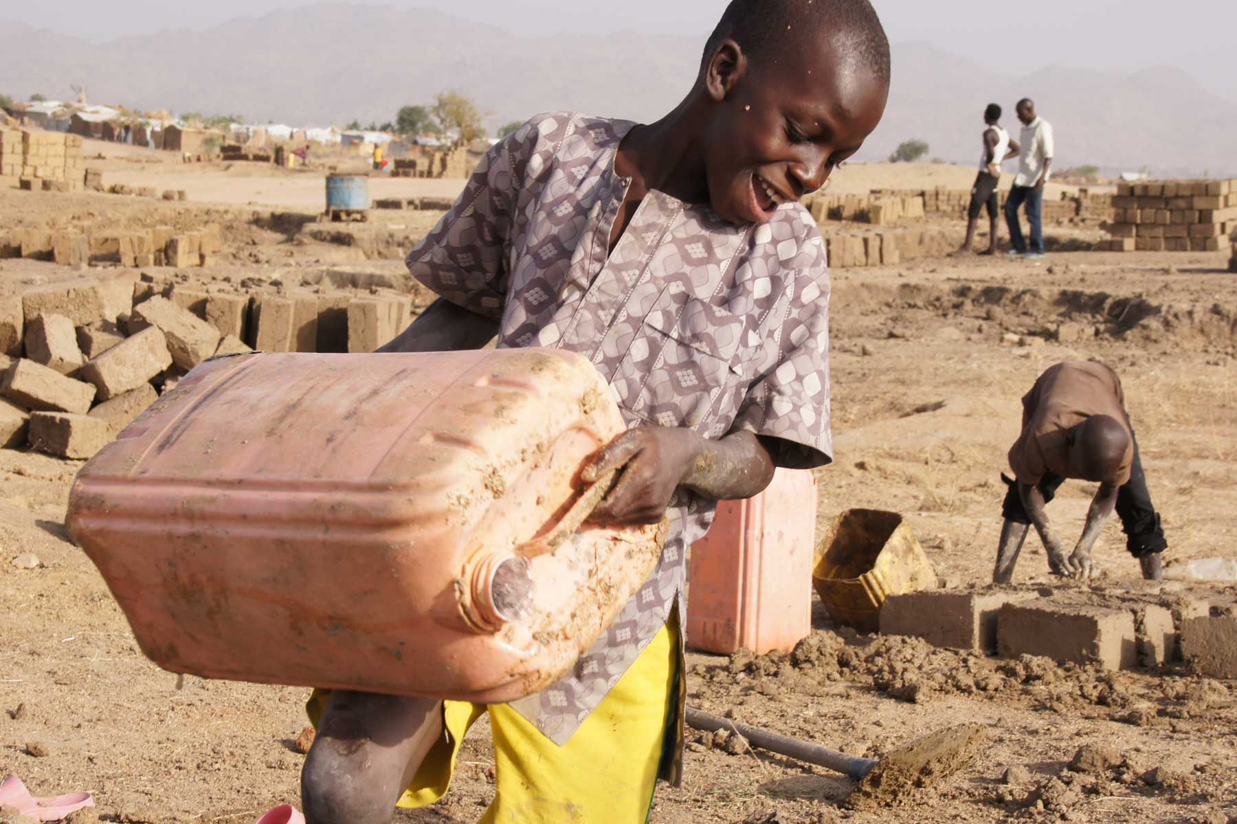 At the tap stand, predominantly women and girls wait to fill their jerry cans to cook and wash for the families.