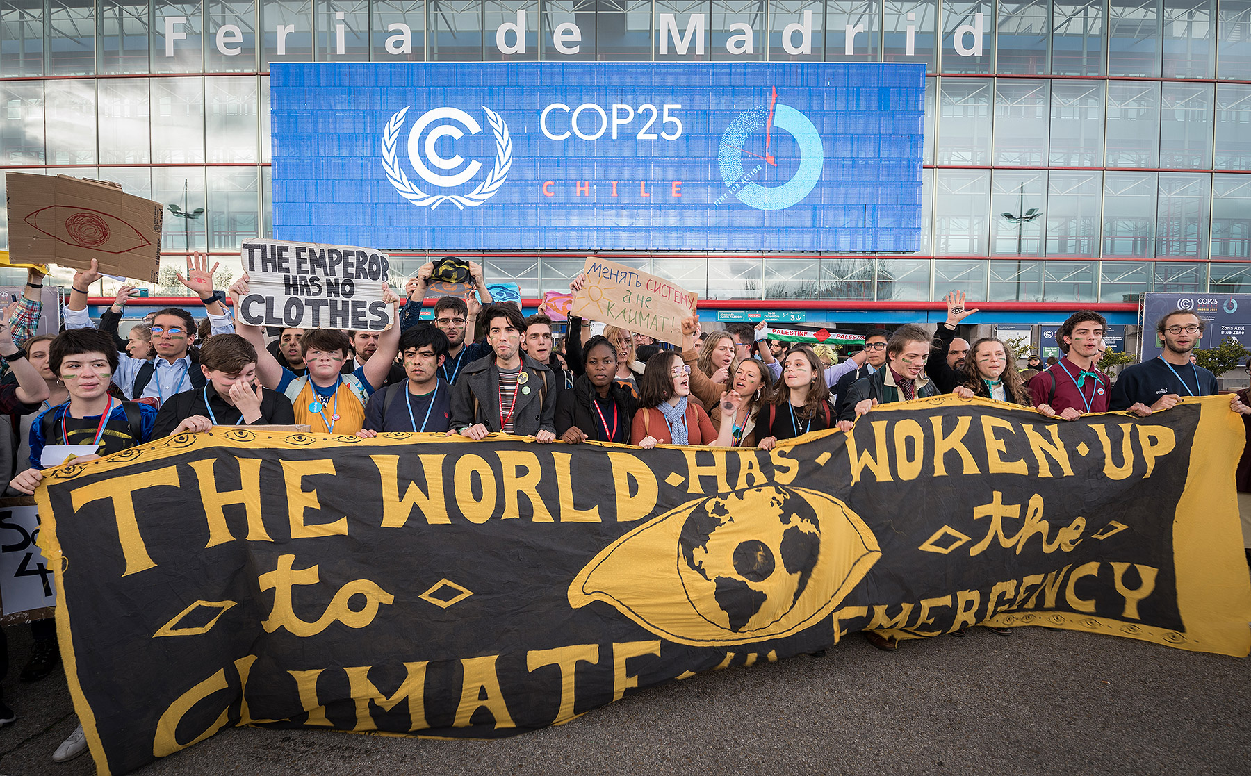 Gathered outside the COP25 venue, young people hold a banner stating 'the world has woken up to the climate emergency'. The question is, have the politicians? Photo: LWF/Albin Hillert