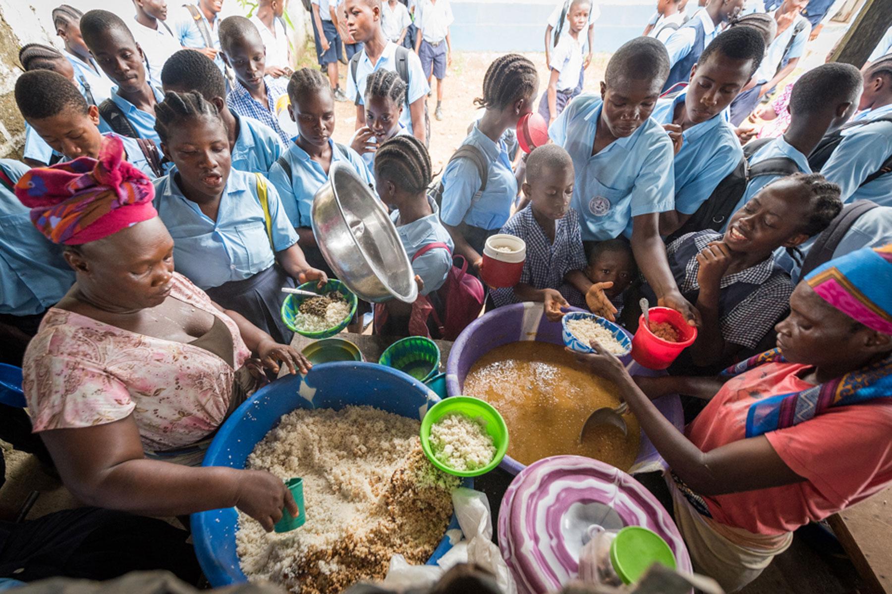 Children gather around a hot meal at Mother Tegeste Stewart.