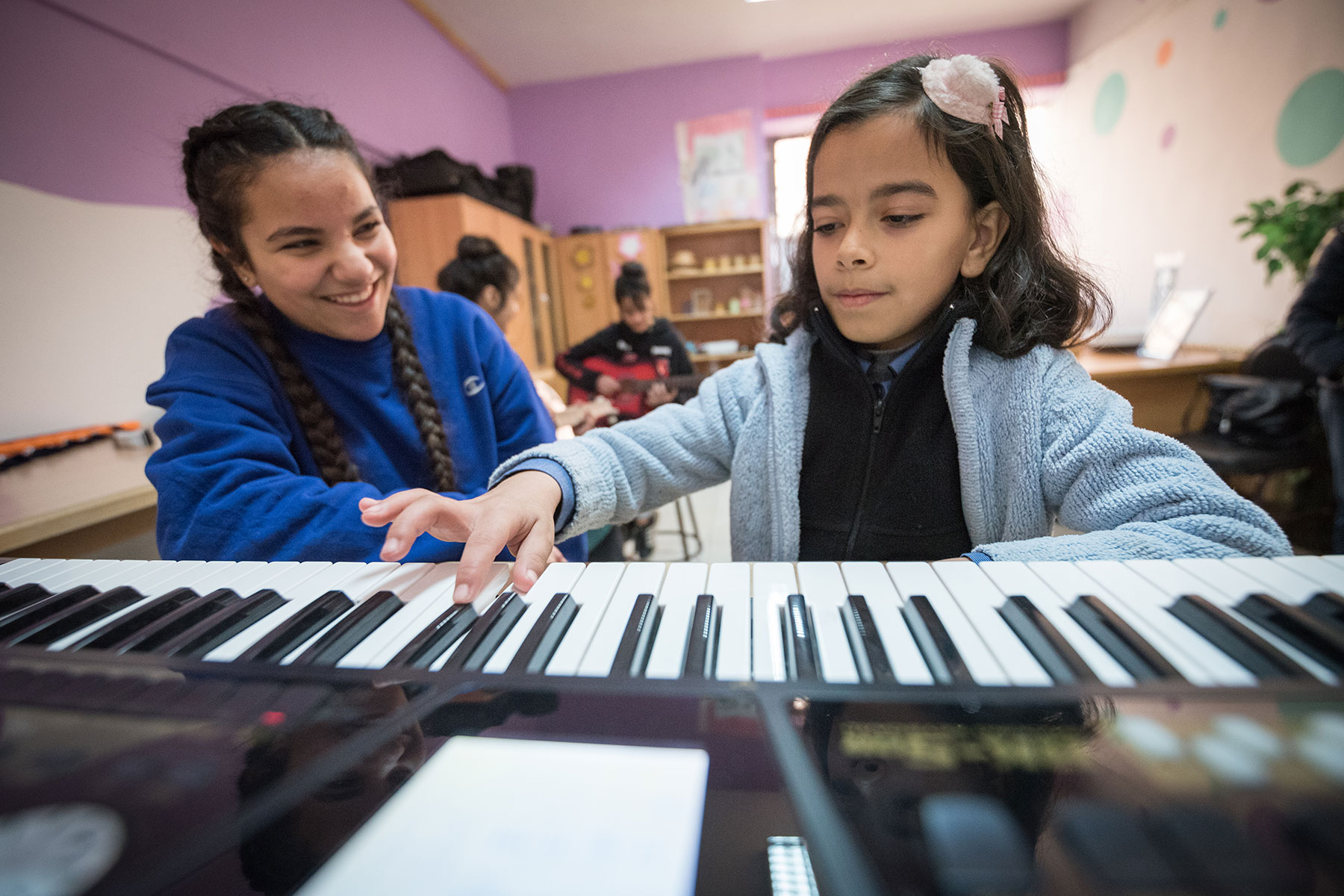 15-year-old Rena Almaharmeh (left) receives piano instructions from ten-year-old Saja (right) in the Talent Room at Rufaida Al Aslamieh Primary Mixed School.