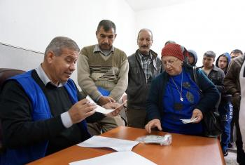 Gorgya Paols, 63, receives a LWF food voucher, entitling her to a carton of food that will last a month. Despite the violence she fled in 2005 and the worsening situation since the ISIS insurgency, her single wish is for peace in Iraq. Photo: LWF/S. Cox