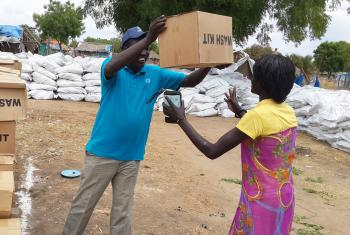 LWF staff provides a displaced woman in Bor with a water, sanitation and health kit. Photo: LWF/South Sudan