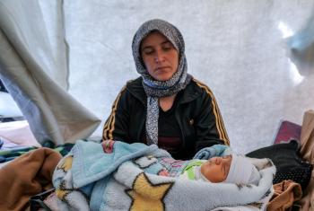 Caption: Kamla Edno and her five-day-old baby, Shahla Edno, at the Berseve 1 camp near the town of Zakho in northern Iraq in December 2014. The baby lies in a plastic crate used to store vegetables. Photo: LWF/ S. Cox