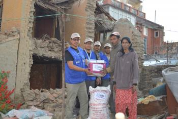 LWF providing relief materials (ready-to-eat food) to a family whose house was destroyed. Credit: LWF Nepal