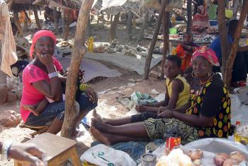 Cecile Endamag (far right) with her nephew and neighbor at her market stand. Photo: LWF/ C. Kästner