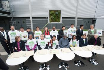 An interfaith group of religious leaders sits in front of empty trays during a public action promoting the Fast for the Climate campaign during the COP21 UN climate summit in Paris, France. Photo: LWF/R. Rodrick Beiler