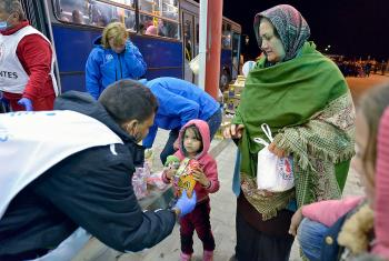 Staff from ACT Alliance member Hungarian Interchurch Aid offer food to a young refugee at Beremend, along Hungary's border with Croatia. Hundreds of thousands of refugees and migrants flowed through Hungary in 2015 on their way to western Europe from Syria, Iraq and other countries. Photo: Paul Jeffrey/ACT