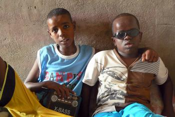 Blind but not illiterate: Mahomed, right, is blind but intelligent and learns about the world through the radio his brother holds. Photo: ALWS/Jonathan Krause
