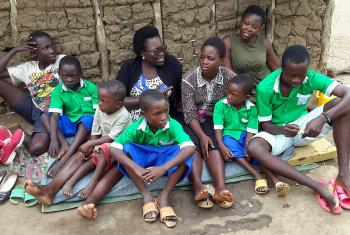 An adult to take charge: Betty Lamunu, center, of LWF Uganda, offered some motherly care to an orphaned family. Photo: LWF Uganda/Z. Asianju