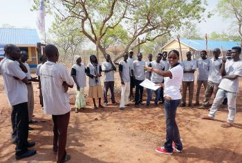 A staff members directs information and communications technology students outside the ICT centre in the Ajuongthok refugee camp where Anne Mwaura works. Photo: LWF/C. Mavenjina