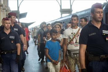 Refugees in Hungary are escorted along a train platform. Photo: MTI