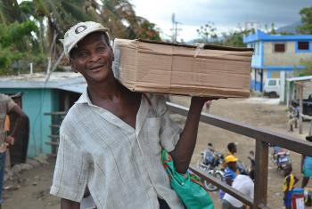 A beneficiary receives a shelter kit in a joint LWF/Diakonie Katastrophenhilfe distribution in Petit Goave. Photo: LWF Haiti