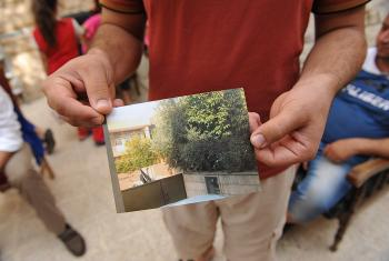A refugee shows a photo of his house. It has been confiscated and marked as IS property. Photo: LWF/M. Rénaux