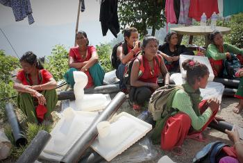Sita, middle, and neighbours sitting among emergency toilet kits. Photo: Lucia de Vries