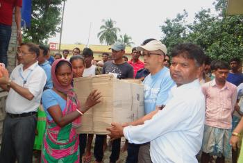 A member of a flood affected family in Jhapa Rural Municipality receives a box containing food, blankets and kitchen utensils provided by LWF Nepal and its partner organization in Jhapa. Photo: LWF/ Prabesh Bhandari
