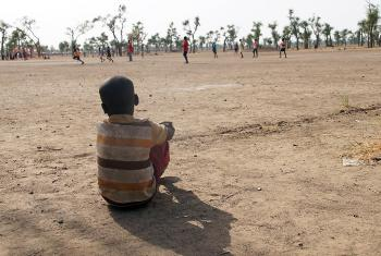 A little boy watches a football game in a child friendly space, Gendrassa refugee camp, South Sudan. Photo: LWF/ C. Kästner