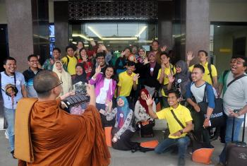 Monk Dhirapunno takes a group photo in front of the conference center in Medan. Photo: A. Yaqin