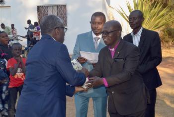 ELCCo Presiding Bishop René Mwamba Sumaili offers a gift to Evangelical Lutheran Church in Tanzania General Secretary Brighton Killewa (left). Third from right is ELCCo General Secretary, Gilbert Ilunga Nkasa Talwa. Photo: LWF/Gracia Rubona