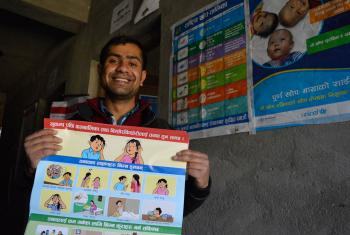 Posters, like the one held by counselor Pradeep Subedi, show the psychological impact of earthquakes on children. Photo: LWF/Lucia de Vries