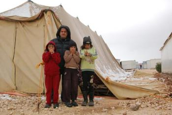 A street leader with his children in front of a half collapsed tent which is used as a Mosque. Photo: LWF/ J. Pfattner