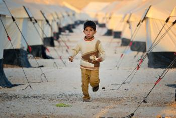 Early in the morning, a boy runs amid the tents in the Zaatari Refugee Camp, located near Mafraq, Jordan. Opened in July, 2012, the camp holds upwards of 20,000 refugees from the civil war inside Syria, but its numbers are growing. Photo: Paul Jeffrey/ACT