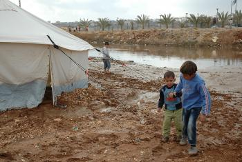 Children walk near flooding in tented settlement Jordan. Photo: Karl Schembri/Oxfam (CC-BY-NC-SA)