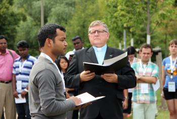 Caption: Benison Kachhap contemplates the significance of being the first young Lutheran to plant a tree in the renowned Luther Garden, in Wittenberg. Rev. Hans Kasch, director of the LWF Center in Wittenberg, looks on. Photo: GNC/LWF/F. Hübner