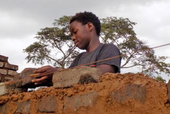 Hawa Andrew constructs a wall. Photo: LWF/ S. Nalubega