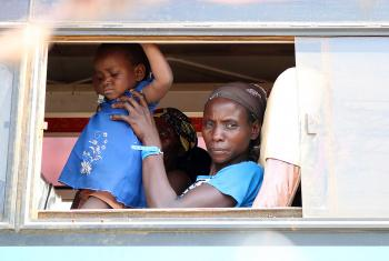 A woman newly arrived from the DRC holds a child as they wait to be moved from the Sebagoro landing site. LWF Uganda is at the frontline of the refugee response. All Photos:  LWF Uganda / S. Nalubega