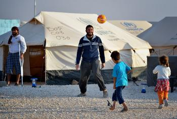 A man plays football with his children in the Zaatari Refugee Camp, Jordan, while another man, wounded in fighting in Syria, looks on. Photo: Paul Jeffrey/ACT