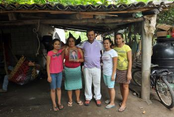 Rigoberto and his family with an image of their son, who was kidnapped on the migration route to the US. Photo: LWF/C. Kästner
