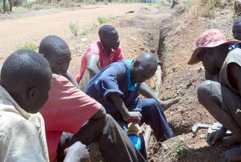 LWF water technicians fix a pipe in Ayilo2 refugee camp, Adjumani district, Uganda. Photo: LWF Uganda