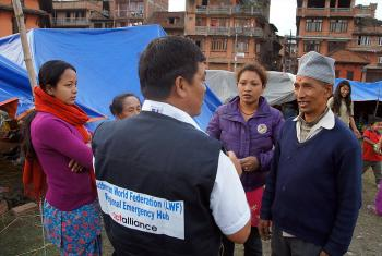 LWF staff member Yadu Lal Shresta (centre), of the LWF Asia emergency hub team, talks to survivors about their living conditions in a camp in Bhaktapur, the worst-affected district of Kathmandu valley. Photo: LWF/C. Kästner