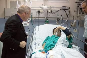 Bishop Munib Younan speaks to an injured boy in the Intensive Care Unit of St. Joseph's Hospital. Photo: D. Hudson/ELCJHL