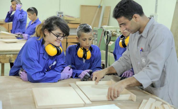 Students watch as a teacher demonstrates a technique in the carpentry workshop. The summer camp encouraged girls and boys to also explore career choices beyond those stereotypically assigned to their gender. Photo: LWF Jerusalem