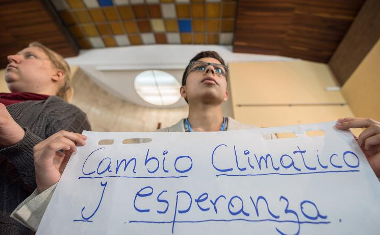 """Cambio Climático y Esperanza"" ('Climate Change and Hope') reads the text, as Lutheran World Federation delegate Sebastian Ignacio Muñoz Oyarzo from the Evangelical Lutheran Church in Chile holds a sheet of paper on which key discussion points have been summarized at an interfaith dialogue in Madrid, 1 December. All photos: LWF/Albin Hillert"