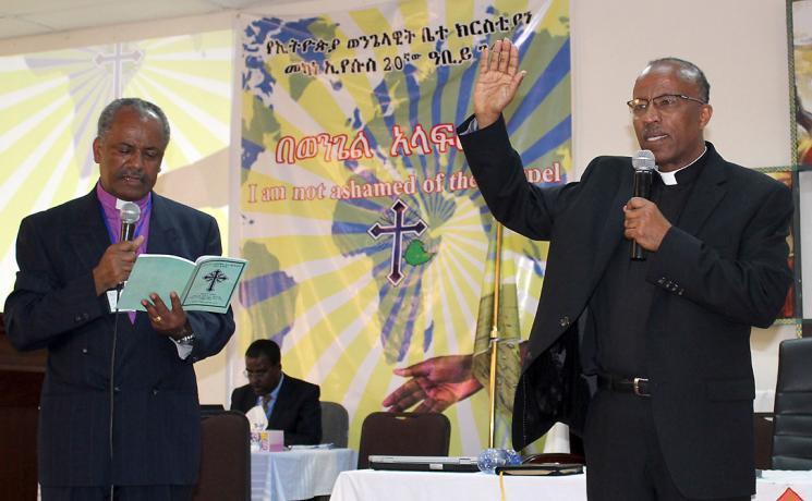 Rev. Yonas Yigezu, right, pledges to lead the Ethiopian Evangelical Church Mekane Yesus with unity and love. On left, outgoing EECMY president, Rev. Dr Wakseyoum Idosa. Photo: EECMY/Tsion Alemayehu