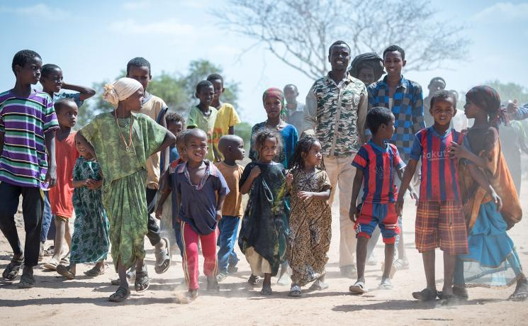 The Lutheran World Federation supports internally displaced people in several regions of Ethiopia, through emergency response on water, sanitation and hygiene (WASH) as well as long-term development and empowerment projects, to help build resilience and adapt communities' lifestyles to a changing climate. Here a group of Oromo internally displaced people move through the Burka Dare IDP site. Photo: LWF/Albin Hillert