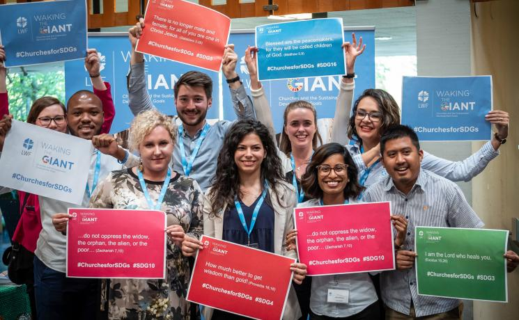 LWF Council youth delegates hold posters at the launch of the Waking the Giant ecumenical initiative in Geneva. Photo: LWF/S. Gallay