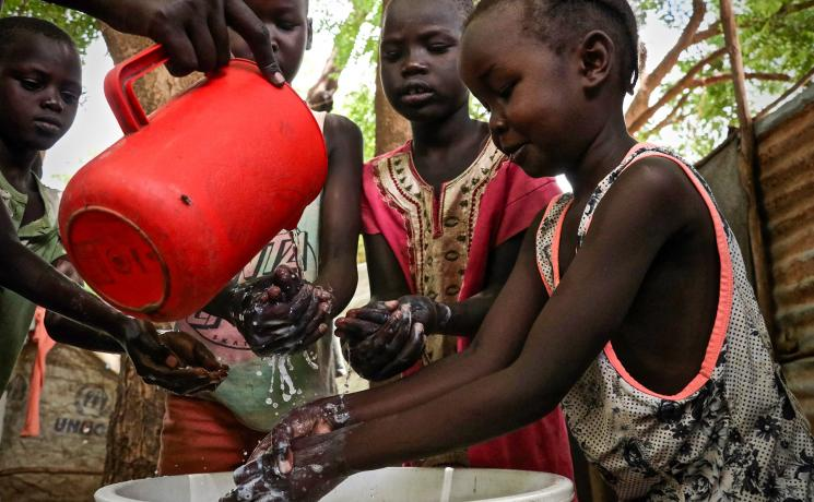Children demonstrate hand washing at Kakuma refugee camp, Kenya. The LWF is the main implementer of education in the camp, and awareness-raising on hygiene is part of that work. The LWF has reinforced hygiene education to prevent the spread of COVID-19 in the camp. Photo: LWF/P. Omagwa
