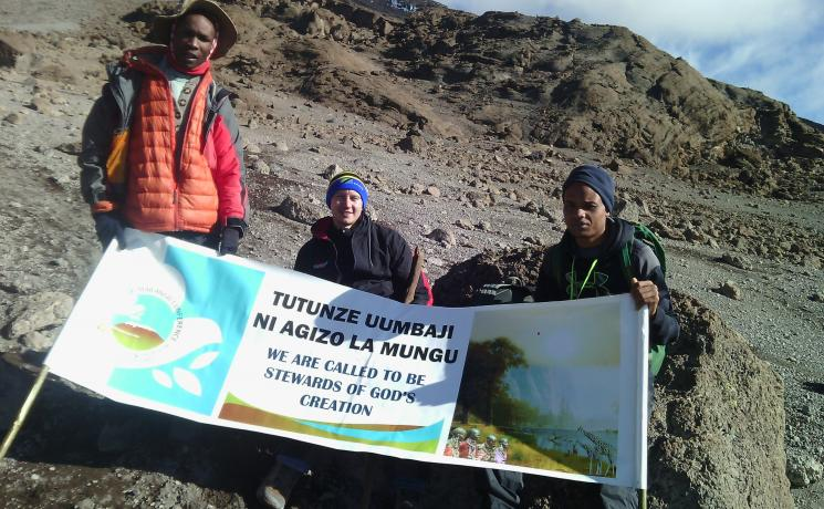 Young Lutherans unfurl the banner they erected at the summit of Mt Kilimanjaro, as the Lutheran African Leadership Conference was being held in Moshi, Tanzania, to raise awareness of the need by Lutherans to protect the environment. Photo: Tsion Alemayehu