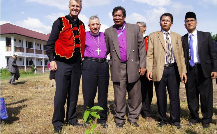 (From left) LWF General Secretary Martin Junge, LWF President Bishop Dr Munib Younan, LWF National Committee in Indonesia Chairperson Bishop Langsung Sitorus and other member church representatives with a Luther Garden partner tree planted at the Ecumenical Center of the Council of Protestant Indonesian Churches in North Sumatra on 15 June 2014. Photo: LWF/C. Kästner