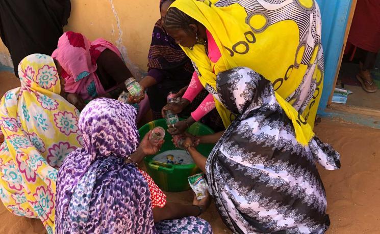Women wash glasses to preserve vegetables in. Photo: LWF/ P. Lo Moro