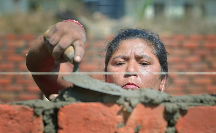 Bhagwati Tamang lays bricks in Jogimara village in central Nepal after the devastating earthquake of April 2015. Following the disaster, the LWF worked jointly with Islamic Relief Worldwide and other partners to provide shelter in remote villages where thousands lost homes and livelihoods. Photo: Paul Jeffrey/ACT