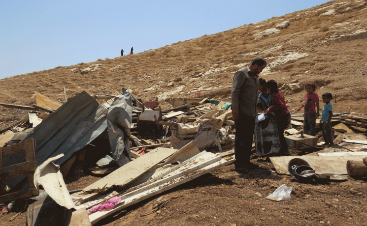 People pick through rubble at the site of a demolition in Wadi Sneysel, in the West Bank near East Jerusalem.