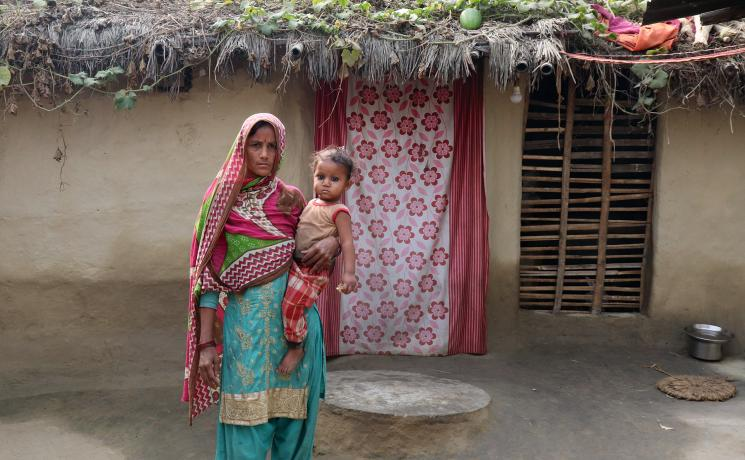 Sakina Khatun holds her youngest child in front of the family home, which needs a better roof and sanitation. All photos: LWF/ Y. Gautam