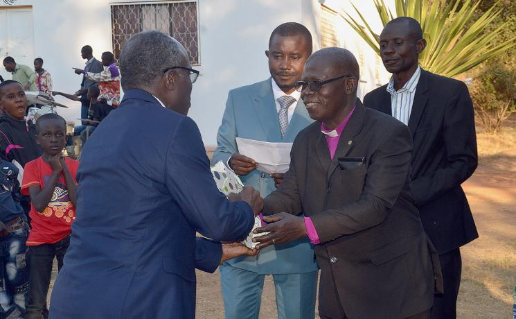 ELCCo Presiding Bishop René Mwamba Sumaili offers a gift to Evangelical Lutheran Church in Tanzania General Secretary Brighton Killewa (left). Third from right is ELCCo General Secretary, Gilbert Ilunga Nkasa Talwa. Photo: LWF/Gracia Rubona
