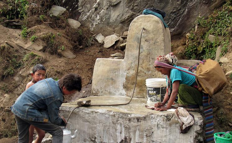 Karmu Tamang from Thangdur, Rasuwa washes bed  sheet of her six months-old baby in the public tap in Thangdur village in Yarsha 6 . LWF Nepal and BATAS foundation Nepal have rehabilitated the water scheme. Photo: LWF/ U. Pokharel